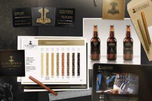 Papper med lgotyp, visitkort, utkast på hemsida och grafisk profil för bryggeriet Sledgehammer Brewing Company. Runtomkring finns ritmateriel så som pennor och linjaler.